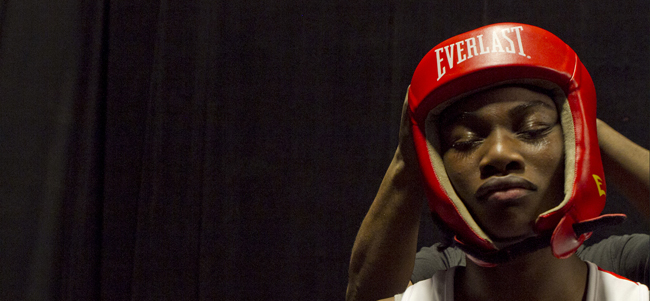 Boxer Claressa Shields is seen preparing for a fight. She stands with her eyes closed as her coach straps protective padding on her head.