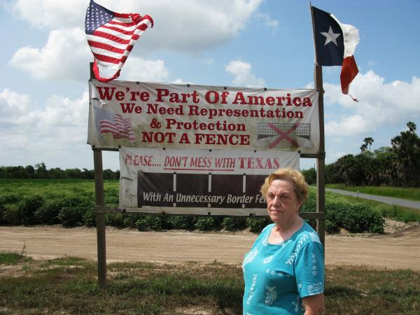 Pamela Taylor in front of her house in Brownsville, TX.  She lives on the Mexican side of the border fence. Photo by John Burnett/NPR.